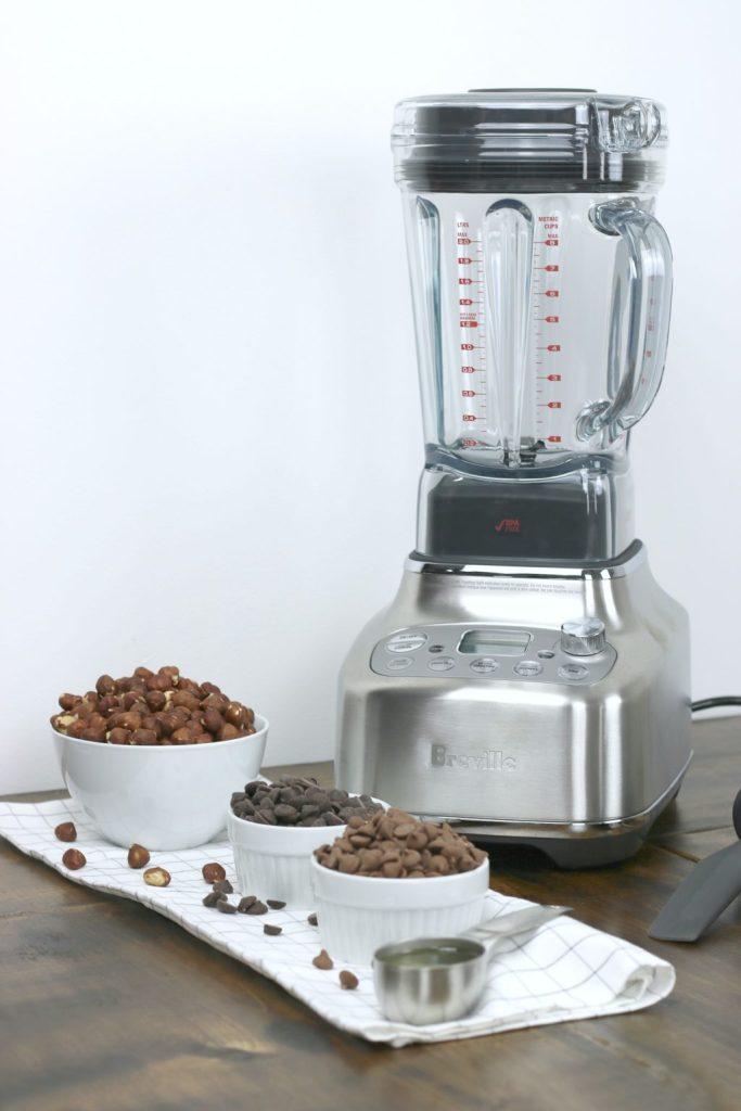 The Breville Super Q blender with 4 ingredients for hazelnut spread recipe. Hazelnuts, dark chocolate, milk chocolate, and peanut oil.