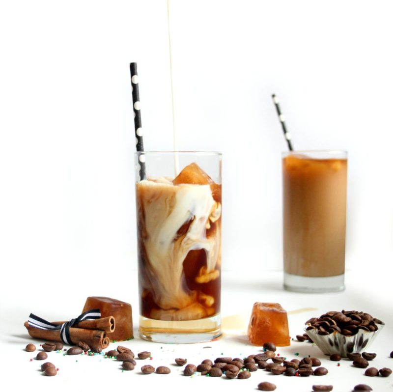 2 tall glasses with polka dot straws with coffee beans and coffee ice cubes.