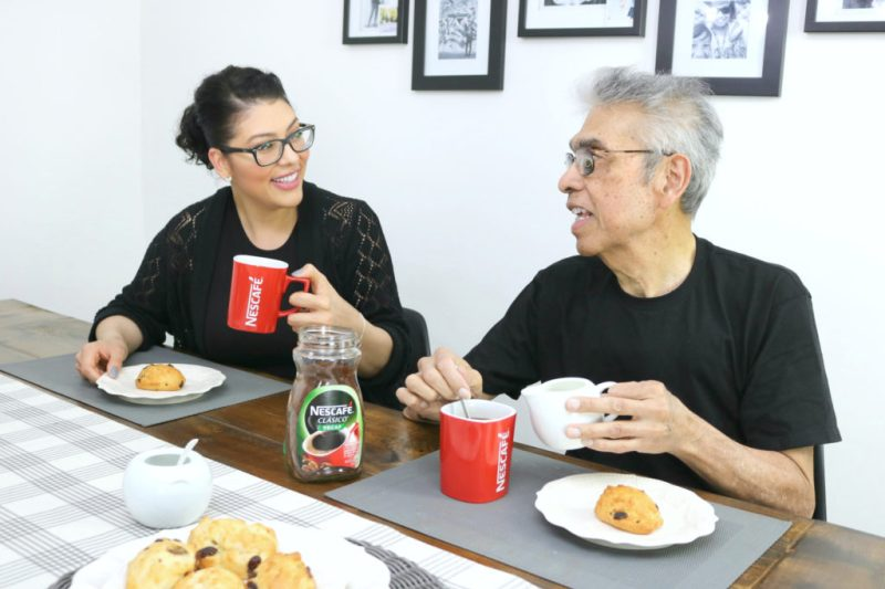 Father and daughter look at each other while the dad adds milk to his NESCAFÉ® CLÁSICO™.