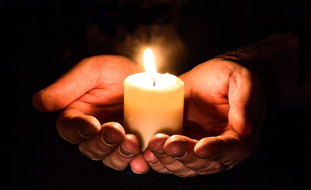 Image of hands holding a beautiful burning candle indicating an absent healing intention