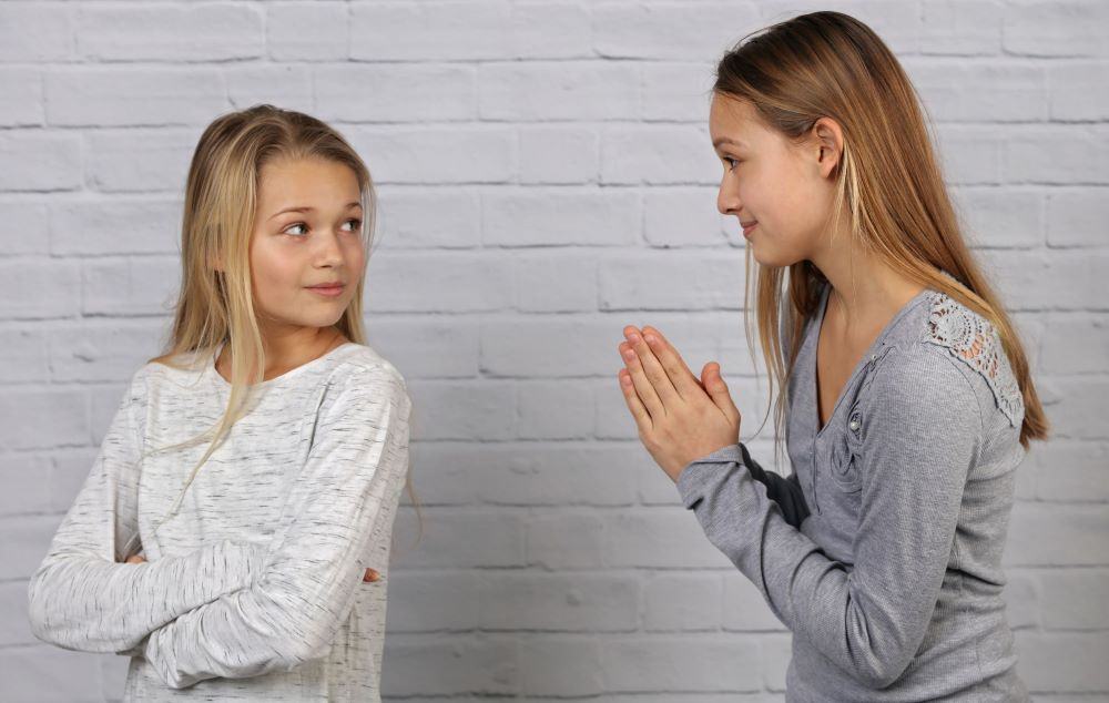 apology- girl apologizing to friend whispers of worth