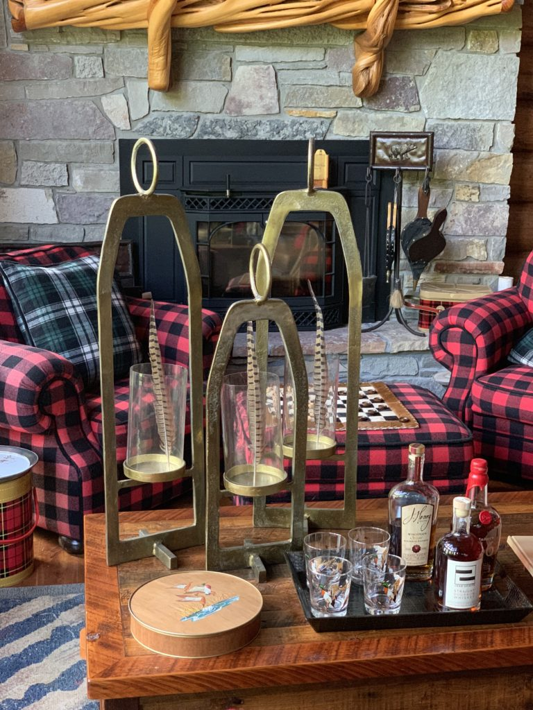 Buffalo Plaid Chairs by the fire, brass hurricane lanterns hold pheasant feathers