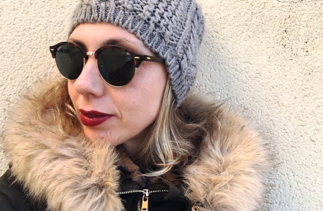 wearing parka wooly hat and rayban sunglasses