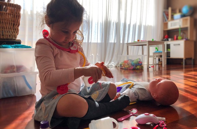 Playing doctors with her dolls - childhood