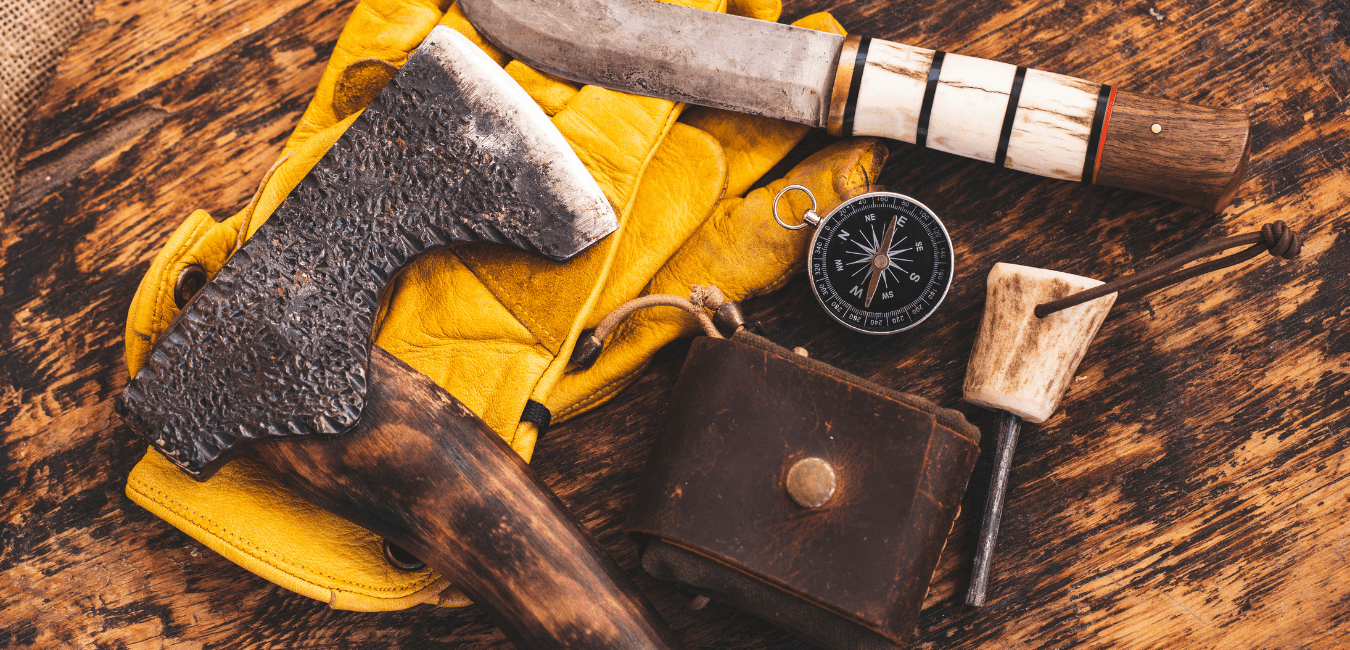 Bushcraft equipment in a wood, including axe, knife, compass and fabric