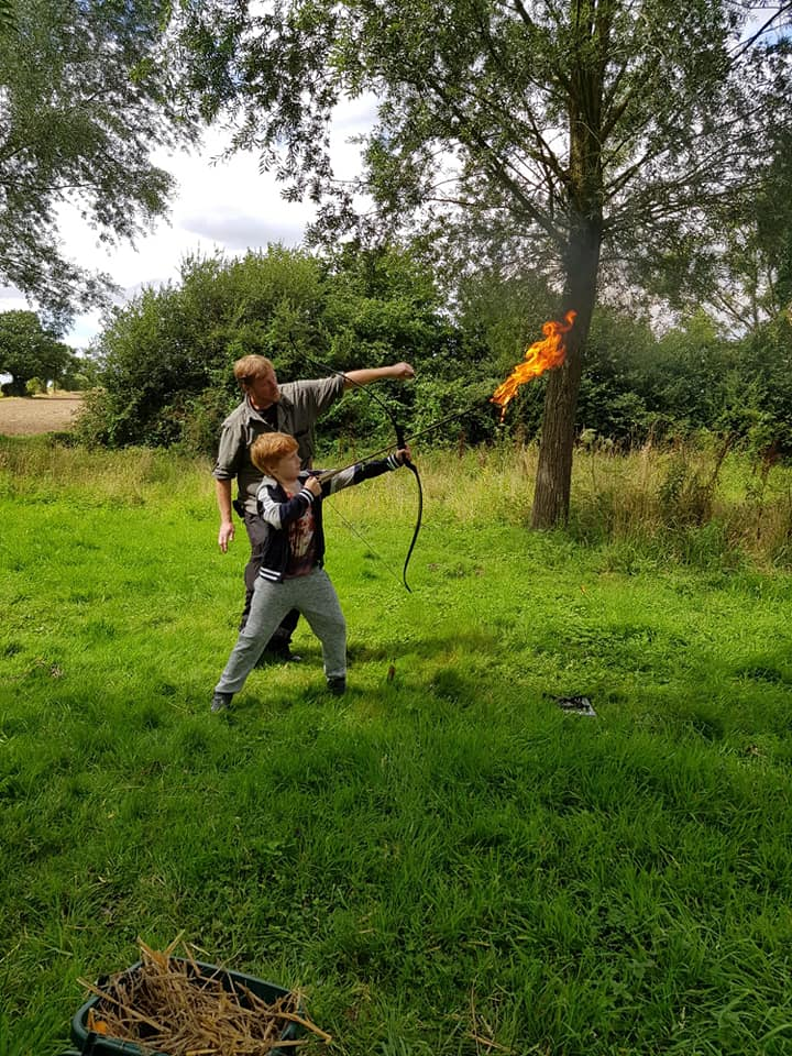 Boy shooting flaming arrow with help from archery coach