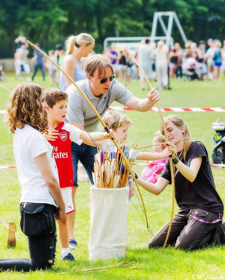 Coaches teaching a young child archery at SWFest festival in Chelmsford