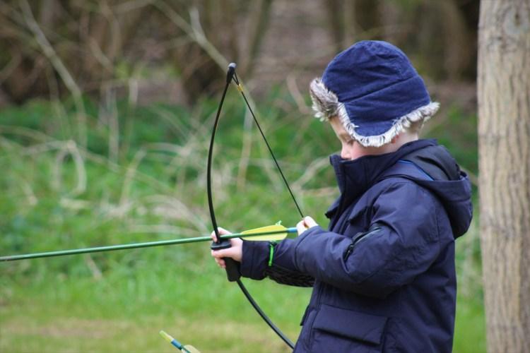 Little boy shooting an arrow with a recurve bow