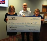 Presenting a check to Carrie Herman, Exec Director for the Kansas Learning Center for Health Inc. is White Eagle President - Rick Blue and Newton Branch Manager, Debbie Morse.