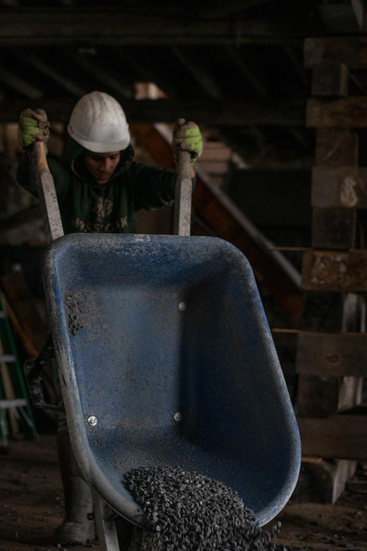 White falcon solutions worker emptying wheelbarrow