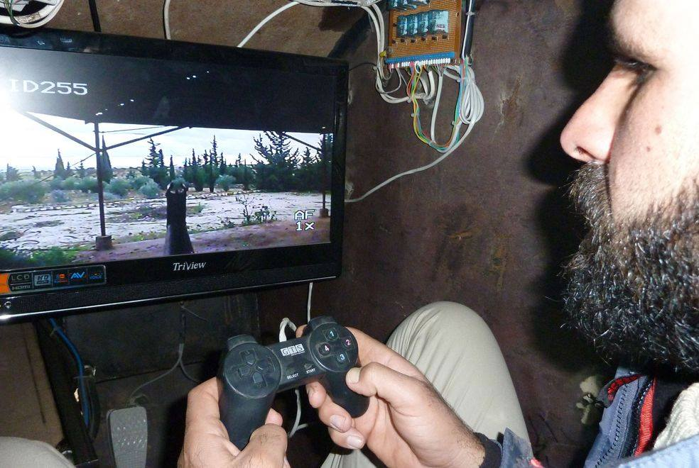 A Syrian Rebel uses a Playstation controller to aim a remote weapon system on his improvised armored vehicle.