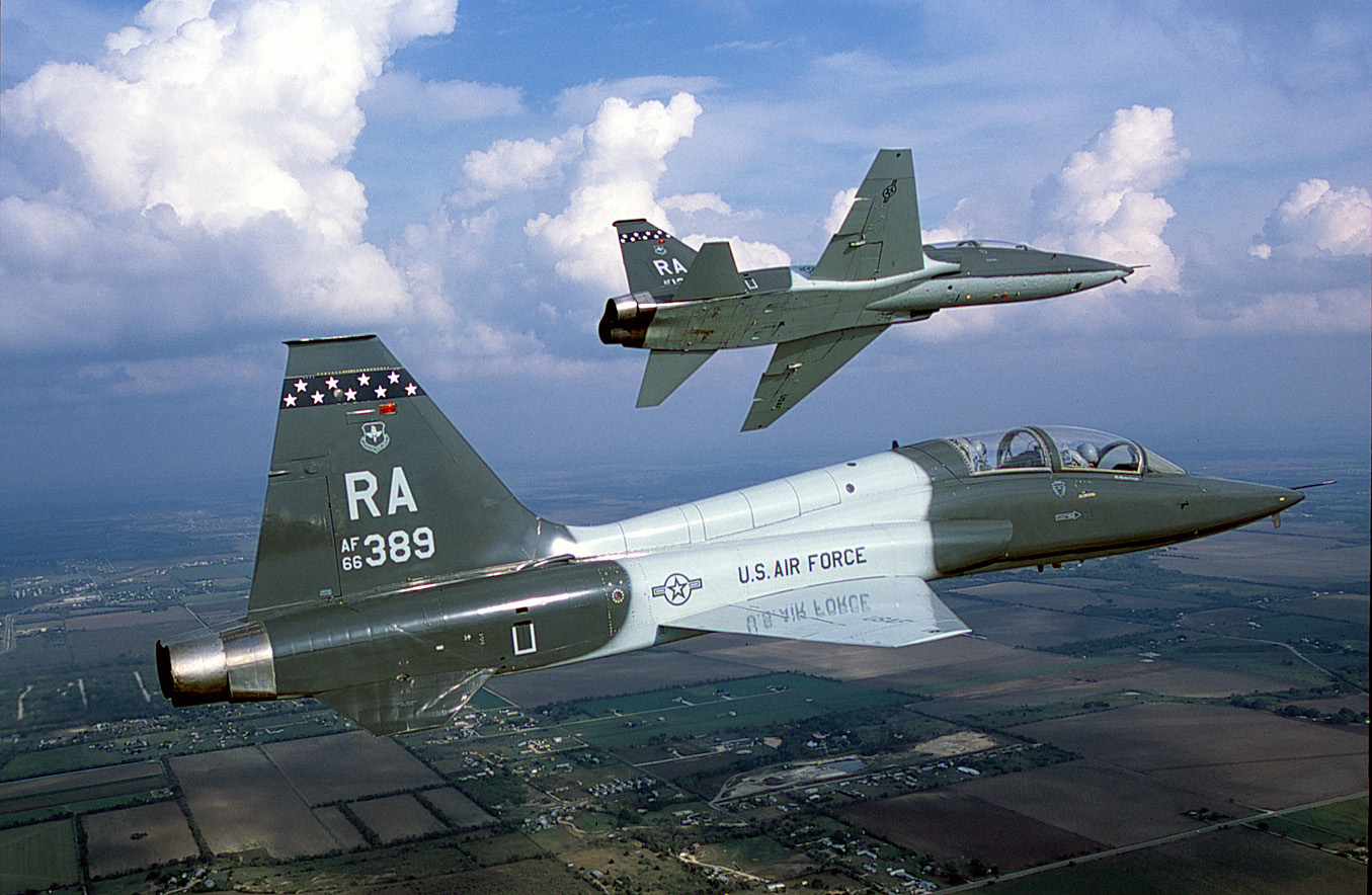 A T-38 Talon trainer flies in formation while its wingman rolls to the left.