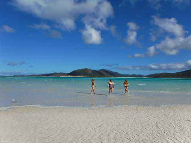 3 girls running into the ocean in the Whitsunday islands