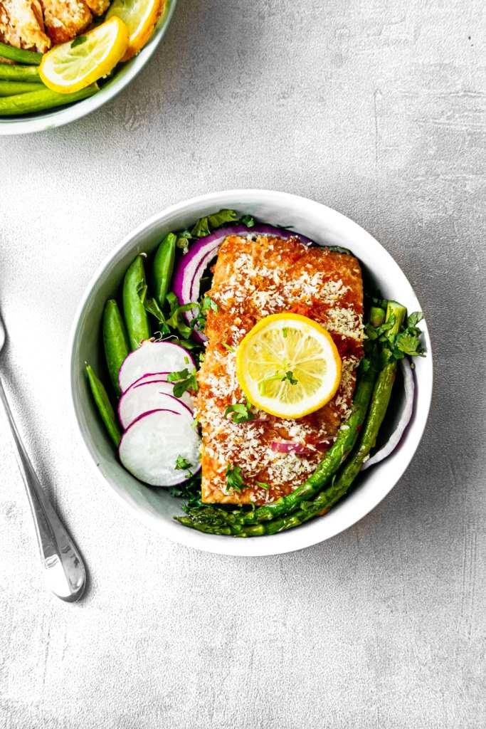 Bowl of crunchy Thai salmon with asparagus, radish, and peas.