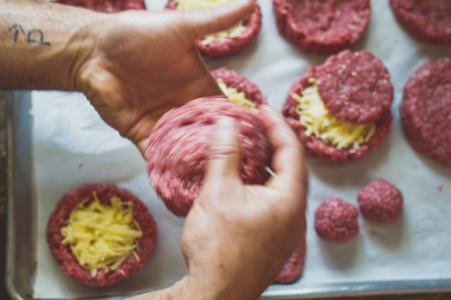 The Juicy Lucy Burger with melted cheese oozing from the center of the patty. Recipe from White On Rice Couple