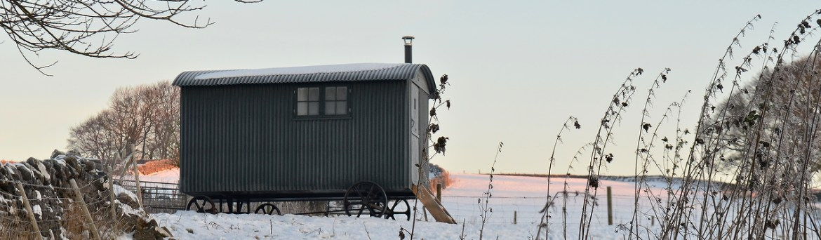 Snow filled field containing shepherd hut