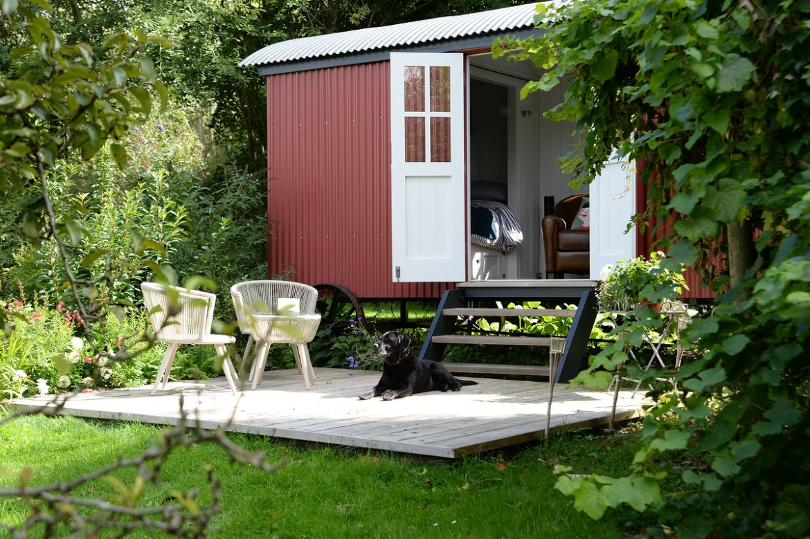Red shepherd hut in pretty English garden