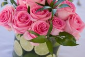 Closeup of centerpiece for wedding with limes and pink roses