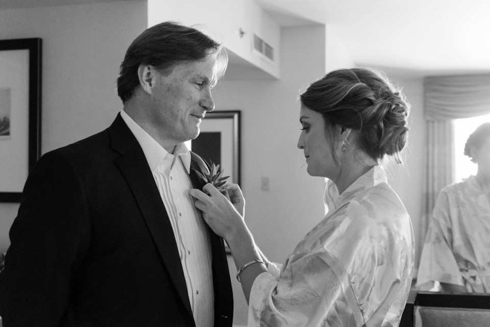 The bride's sister pinning a boutonniere on her dad at the Palmer House in Chicago IL