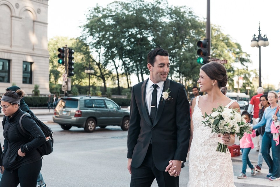 Couple looking at one another and smiling as they cross a busy Chicago intersection