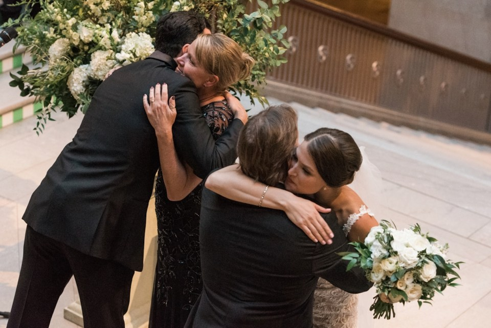 Bride and groom hug the bride's parents during their wedding ceremony at the Art Institute of Chicago