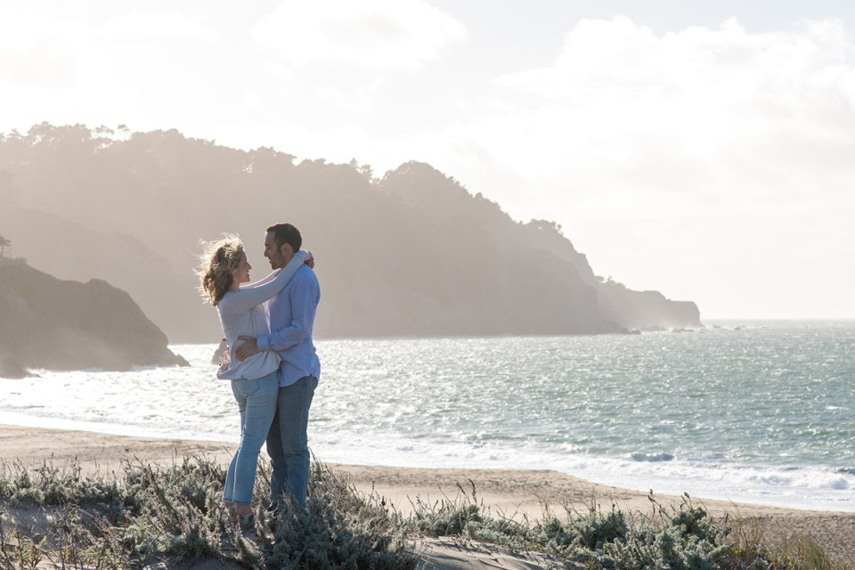 Couple standing on a sand dune in the wind at Baker Beach