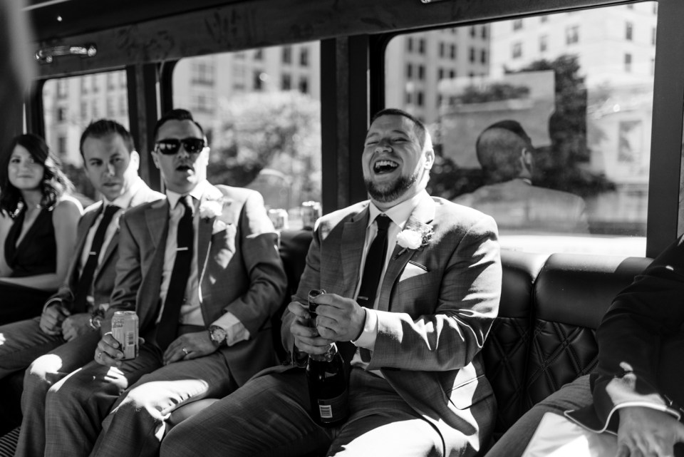 Best man laughs while opening a bottle of champagne on the party bus