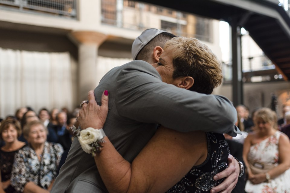 Groom gives his mother a hug during the ceremony at Artifact Events