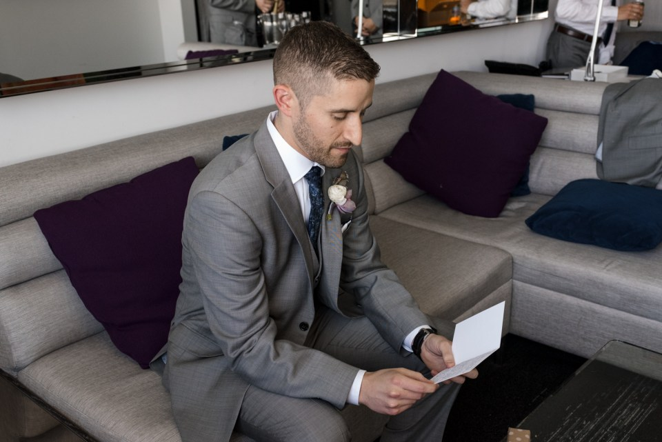 Groom reading a letter from the Bride at the W Hotel Lakeshore