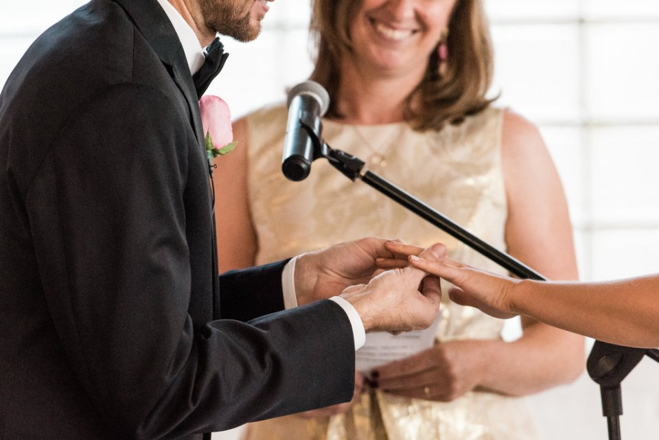 Closeup of groom putting on the bride's ring at Room 1520 in Chicago IL