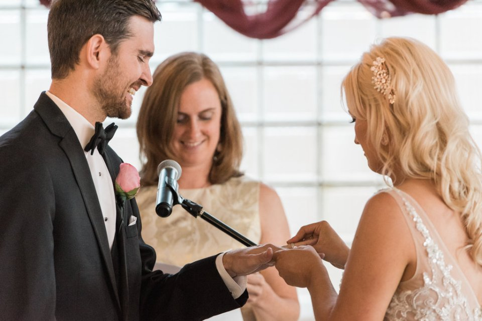 Bride putting on the groom's ring at Room 1520 in Chicago IL