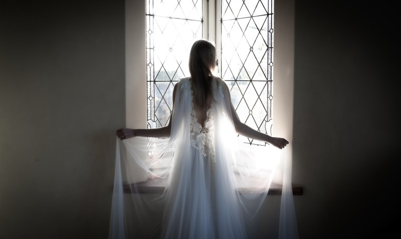 A woman with blonde hair and wedding a white wedding gown stands in front of a stained glass window