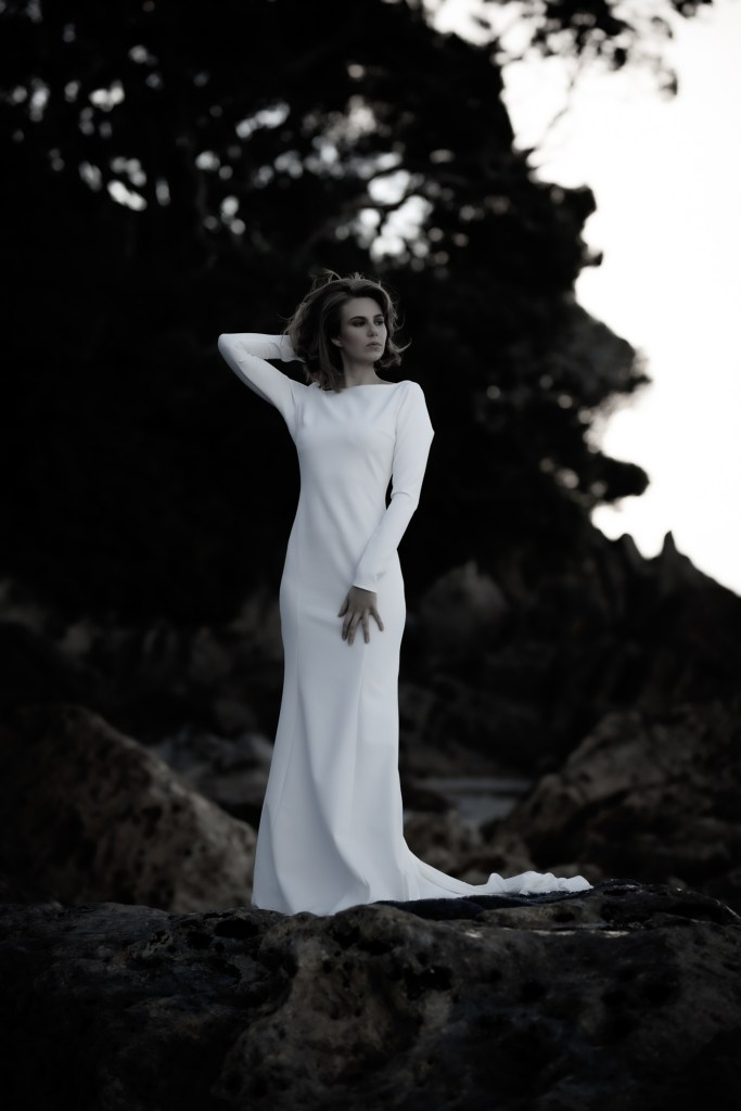 A woman stands on a rock in Tauranga in one of the bridal gowns from White Silk Bridal