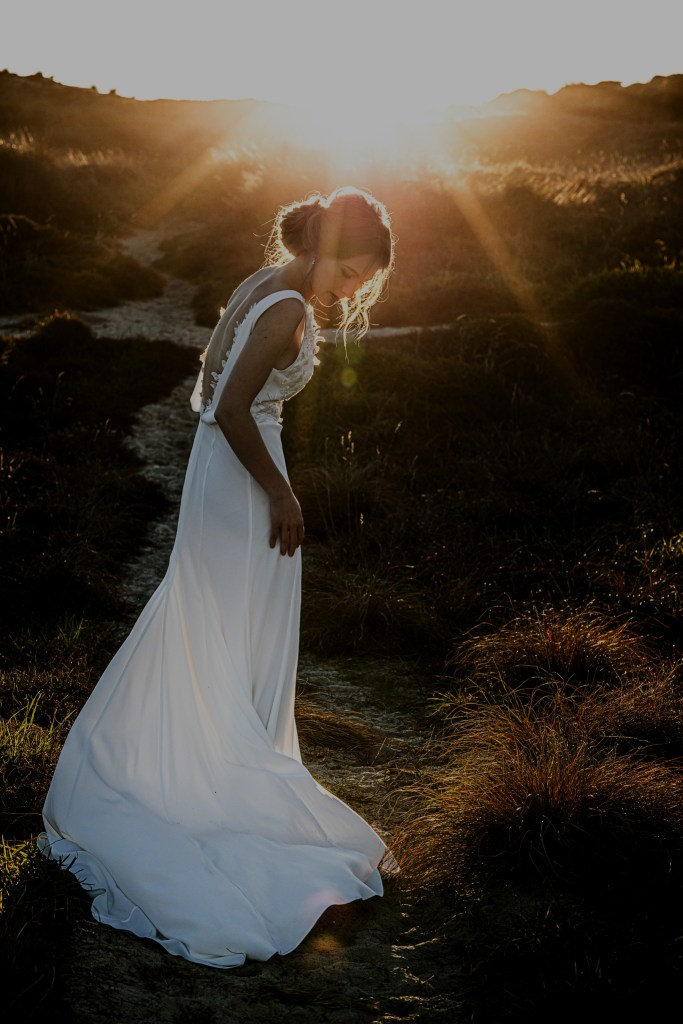 A woman on sand dunes in Tauranga wears a wedding gown by White Silk Bridal