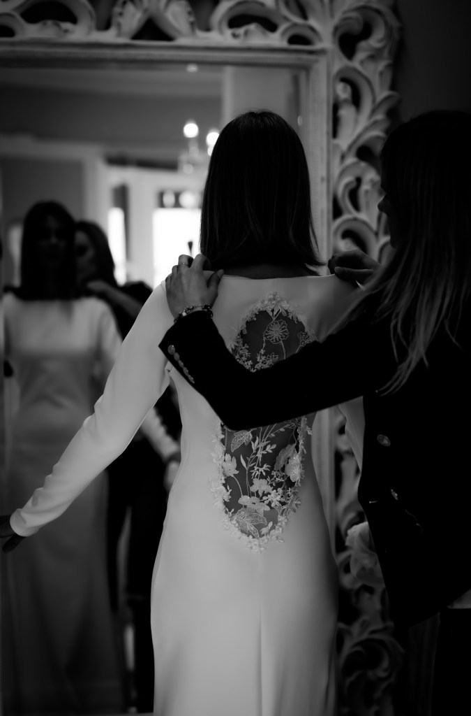 A woman wearing a white bridal gown stands in front of a mirror at Tauranga designer White Silk Bridal