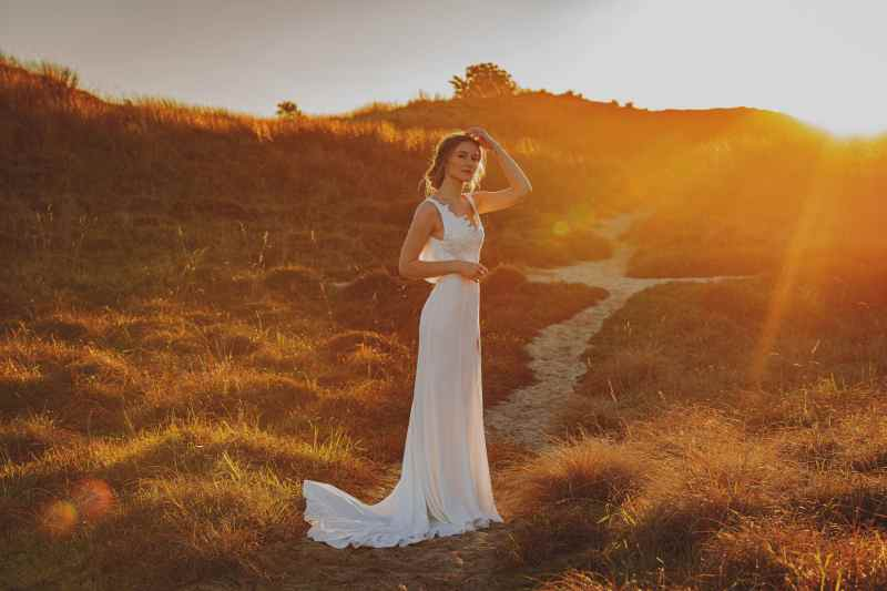 A woman in a white bridal gown stands in the sand dunes in Tauranga