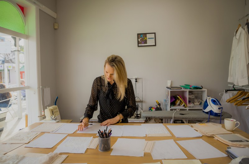 Wedding gown designer Nicky Hayward stands at her work table, designing wedding gowns