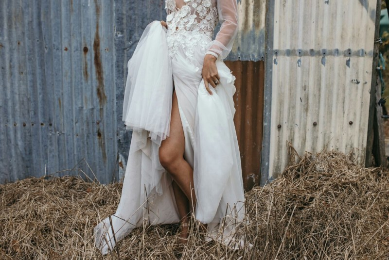 A woman in a wedding gown stands in front of a barn