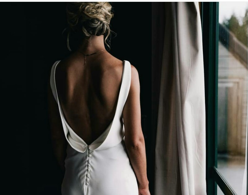 A woman with blonde hair stands by a window whilst wearing a bridal gown by White Silk Bridal of Tauranga