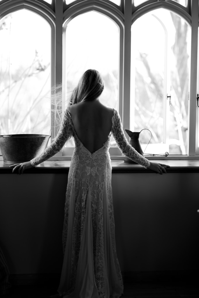 A woman in a one of the wedding gowns from White Silk Bridal stands in front of a window near Tauranga