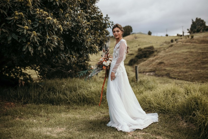 A young woman wearing a wedding dress by Tauranga designer White Silk Bridal holds flowers in a field
