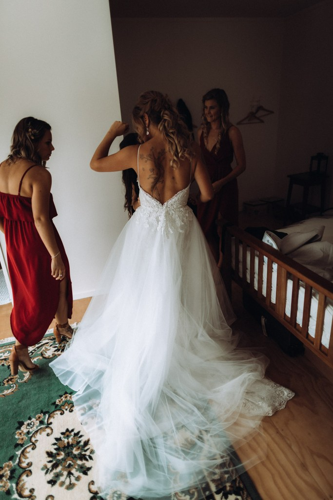 A bride in a wedding gown is helped by her bridesmaids