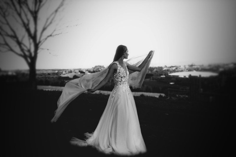 A woman stands in the countryside wearing a bridal gown from White Silk Bridal of Tauranga