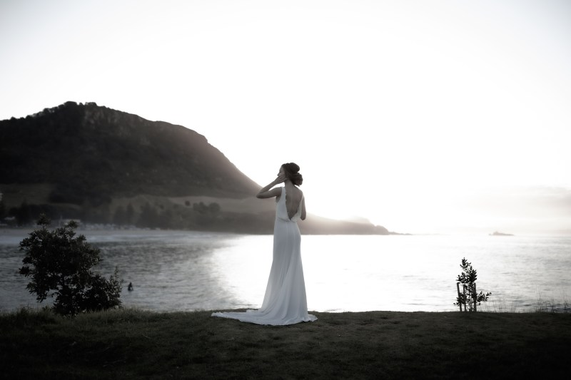 A young woman stands by the sea at Mount Maunganui whilst wearing a white wedding dress