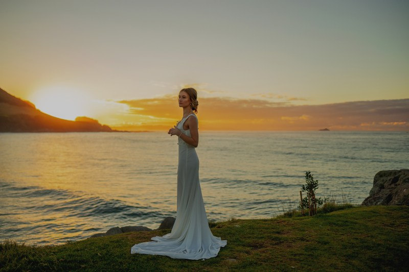 A young woman wearing a white wedding gown stands near Mount Maunganui Main Beach