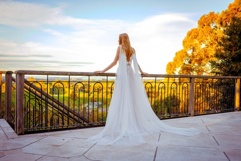 A woman wearing a white bridal gown looks towards Tauranga and the countryside