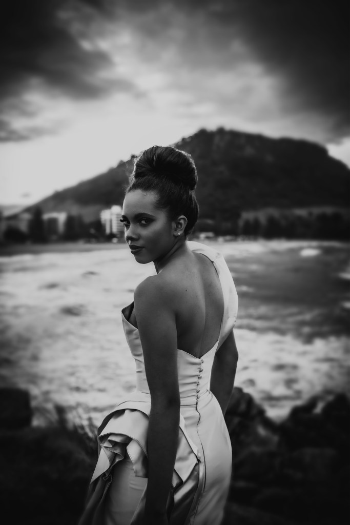A woman stands by the sea in Tauranga wearing one of the designer bridal gowns by White Silk Bridal Couture