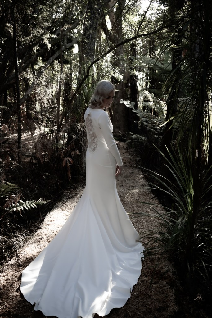 A woman on a pathway in Tauranga wearing a designer bridal gown