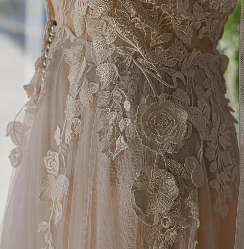The intricate details of a designer wedding gown seen close up