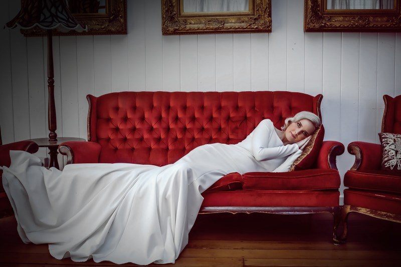 A woman wearing one of White Silk Bridal Couture's bridal gowns lies on a sofa in Tauranga.